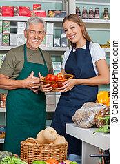 verticaal, van, verkoopster, vasthouden, plantaardige mand, staand, met, mannelijke , collega, in, supermarkt