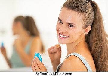 verticaal, van, vrolijke , jonge vrouw , met, dentale floss