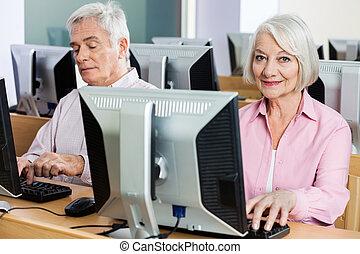 verticaal, van, vrolijke , oude vrouw, het gebruiken computer, in, klaslokaal