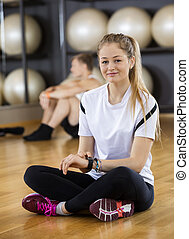verticaal, van, vrouw, gebruik, activiteit, tracker, terwijl, zittende , in, gym