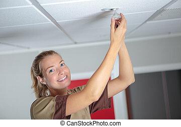 verticaal, van, vrouw, het veranderen van lightbulb