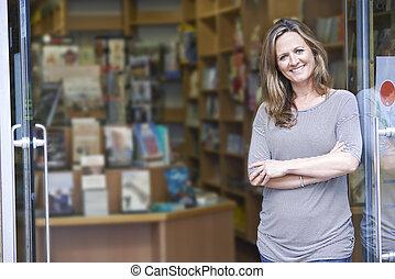 verticaal, van, vrouwlijk, boekhandel, eigenaar, buiten, winkel