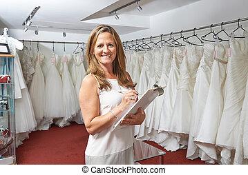 verticaal, van, vrouwlijk, bridal, winkel, eigenaar, met, de kleding van het huwelijk