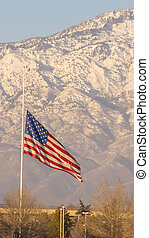 Vertical American flag and building with Mount Timpanogos and sky in the background