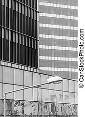 Vertical background with building windows. Black and white architecture abstracts from office buildings and public lamp in front.