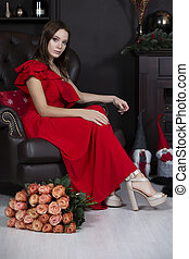 Vertical beautiful model in an armchair. Luxury girl sitting on a leather chair with a bouquet of roses. Young woman in a red dress