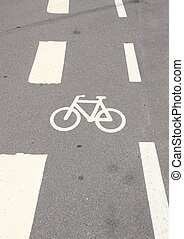 Vertical bicycle sign on asphalt with white stripes