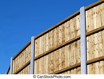 Vertical board fence panels with concrete posts against blue...