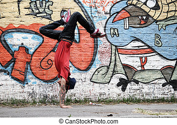 A performing Hip Hop Dancer in front of a Graffiti wall.