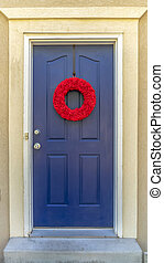 Vertical Bright red wreath on the blue front door of a home with outdoor wall lamp