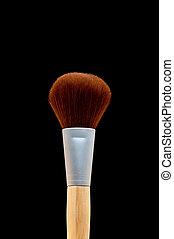 vertical close up of a make-up brush on black