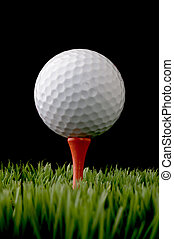 vertical close up of a white golf ball on a tee on black