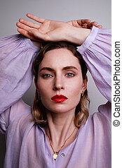 Vertical close-up of beautiful young woman in purple shirt posing with hands up on the white background.