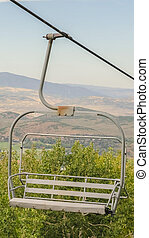 Vertical Close up of chairlift with aerial view of Park City ski resort during off season