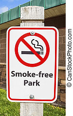 Vertical Close up view of a Smoke Free Park sign agianst a building with stone wall