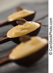 vertical coffee mousse in a dark chocolate spoon.
