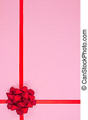 Vertical composition with decorative red ribbon bow on pink background with copy space for text. Giving presents concept. Greeting card or holidays sale background. Selective focus