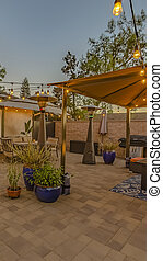 Vertical Cozy stone patio with string of lights over a covered seating and dining area