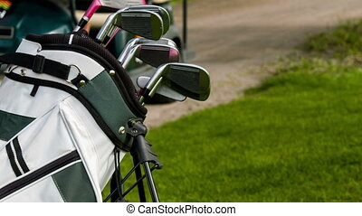 Vertical dolly shot of golf equipment and golf car