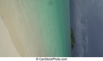 Vertical footage of lagoon sea and beach with small island...