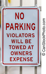 Vertical frame Close up of No Parking sign on awhite metal gate with building in the background