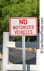 Vertical frame Close up view of a No Motorized Vehicle sign against a road with a white gate