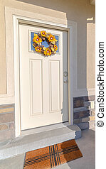 Vertical frame Front door of modern home with sunflower wreath