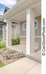 Vertical frame Front porch of modern home with welcome sign