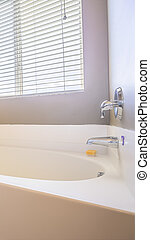 Vertical frame Home bathroom interior with bathtub in front of the window with blinds