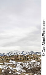 Vertical frame Panorama of residential area and road on a hill against cloudy sky in winter