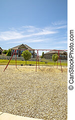 Vertical frame Playground with swings and picnic pavilion under blue sky on a sunny day