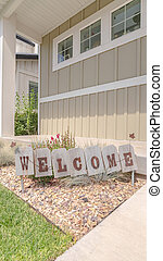 Vertical frame Welcome sign in front garden of traditional home