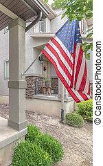 Vertical Front door of suburban home with American flag