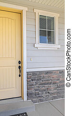 Vertical Front veranda of suburban home with a yellow door