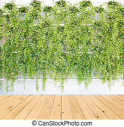 vertical green plant pattern in many black pot on wood floor...