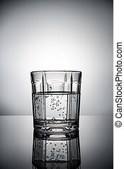 glass of water with bubbles on grey background