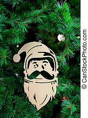 Vertical Image of a Wooden Santa Claus Ornament Hanging on Christmas tree