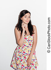 Vertical image of brunette woman in dress looking at camera