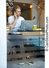 Vertical image of Calm curly business man using smartphone