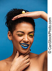Vertical image of fancy mulatto woman with colorful makeup and curly hair in bun posing on camera with playful look isolated, over blue wall