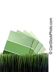 Vertical image of green paint chip samples on green grass with white space for copy