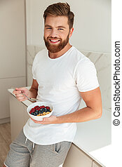 Vertical image of happy bearded man eating fruit