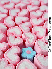 Vertical Image of Many Pastel Pink and White Heart Shaped with Only One Pastel Blue Flower Shaped Marshmallow Candies