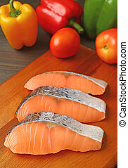 Vertical image of raw salmon slices on wooden cutting board with fresh vegetables
