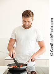 Vertical image of smiling bearded man cooking vegetables