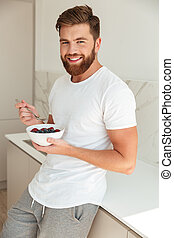 Vertical image of smiling bearded man eating fruit