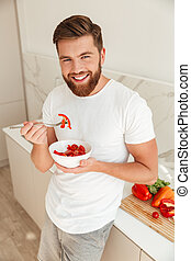 Vertical image of Smiling bearded man eating vegetables