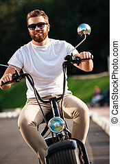 Vertical image of smiling bearded man in sunglasses