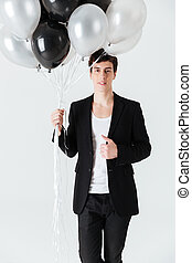 Vertical image of Smiling man holding air balloons