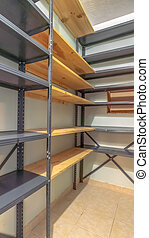 Vertical Interior of a small empty closet with metal and wood shelves for clothes